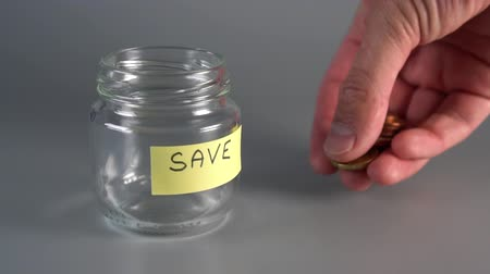 горсть : Hand lays out coins cents and euros near a savings glass jar with a sticker and SAVE inscription. Concept of saving money for the future. slow motion