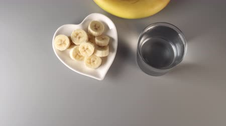 Sliced and whole bananas. On a white plate. On a gray background. Misted with clean water. The concept of a healthy lifestyle