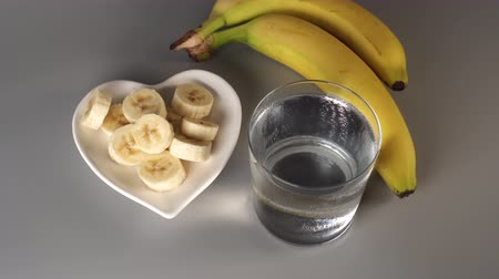 útil : Sliced and whole bananas. On a white plate. On a gray background. Misted with clean water. The concept of a healthy lifestyle