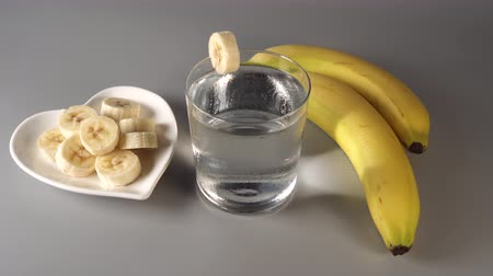 Sliced and whole bananas. On a white plate. On a gray background. Misted with clean water. Fruit diet concept