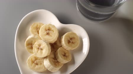 útil : Sliced bananas. On a white plate. On a gray background. Misted up with clear water. The concept of dietary fruit ecological nutrition