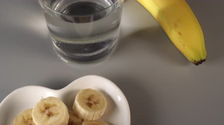 proutěný : Sliced and whole bananas. On a white plate. On a gray background. Misted with clean water. Fruit diet concept