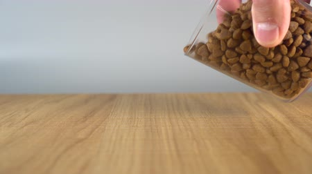 Mans hand pours a bunch of cat food on a wooden table from a glass cup