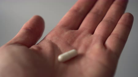 capsulas : The palm of a hand with a white medical capsule extends. The capsule falls into the zone of sharpness. On a gray background. Drug solution to a painful condition