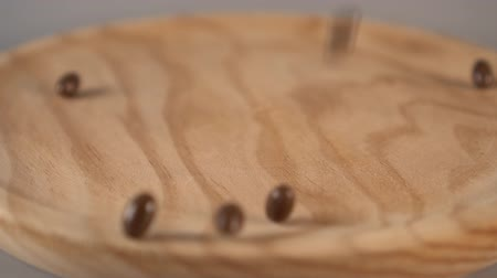 suplemento : Dark medicine capsules fall on a wooden surface on a gray background. Slow motion