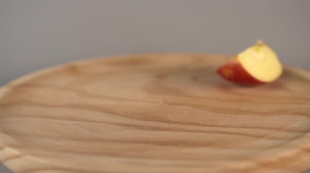 Hand takes half a ripe red apple and lays it back bitten on a wooden surface. Slow motion