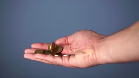 alms : Coins fall in a hand on a blue background. The concept of good luck and professionalism in business Stock Footage