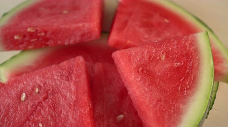 rind : Sliced watermelon spins on a wooden surface. The taste of fresh summer. Thirsty treat