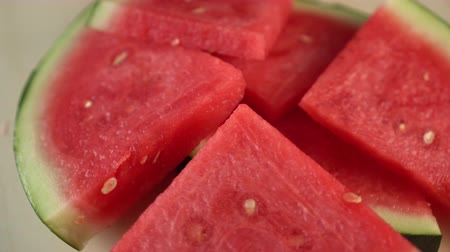 rind : Slices of watermelon spin on a wooden surface. Red juicy pulp for goodies