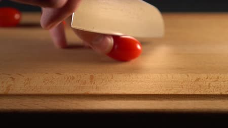 チェリートマト : The cook cuts a ripe cherry tomato into two halves on a wooden surface. On a black background. Slow motion. Cooking Vegetable Diet Meals