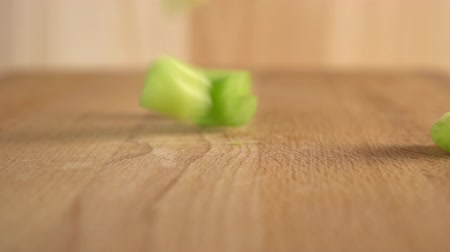 stonky : Sliced celery pieces fall on a wooden surface. Slow motion The use of the healing properties of fresh vegetables
