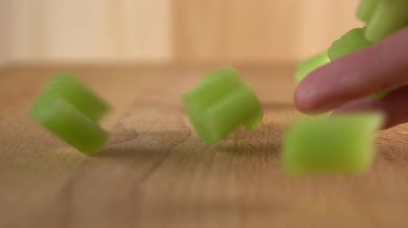 stonky : A cooks hand spills juicy chopped celery slices onto a wooden surface. Slow motion Cooking vegetable salad