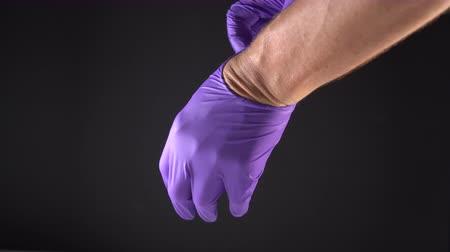 guantes de latex : The man unfolds new blue protective gloves and puts on his left hand. Preparation for the work of a medical worker, nurse