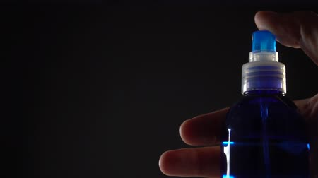 ar : The hand presses the button of the blue spray and the spray fly forward under pressure on a black background