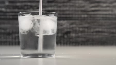 охлажденный : A white drinking tub stirs water with ice cubes in a glass cup. Slow motion. Black and white background