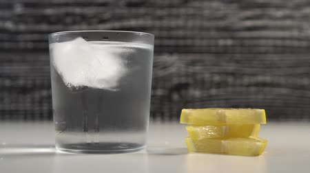 lemoniada : Ice cubes move with water in a misted glass on a black and white background. On a table are slices of fresh lemon