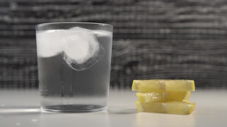 охлажденный : Ice cubes move with water in a misted glass on a black and white background. On a table are slices of fresh lemon