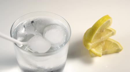 охлажденный : Ice cubes and a tube spinning in a steamed glass on a white background. Next lay slices of juicy lemon