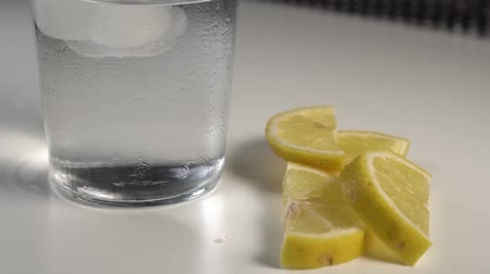 охлажденный : Ice cubes move with water in a misted glass on a white background. On a table are slices of fresh lemon
