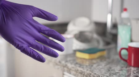 dezenfekte etmek : Young man in clothes pulls on his left blue protective glove for washing dishes in the kitchen sink Stok Video