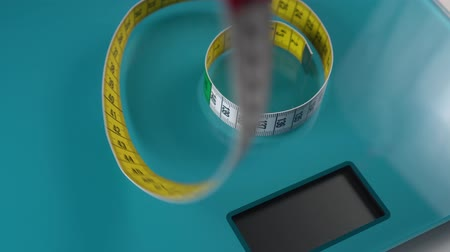 obesity : A multi-colored centimeter descends on top of the rings on the aquamarine floor scales. Diet tools Stock Footage