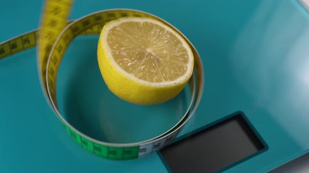 overweight : A multi-colored centimeter descends in rings around a lemon on an aquamarine floor scale. Tools for keeping fit, dieting