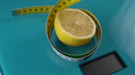 centímetro : A multi-colored centimeter rises in a spiral around a lemon from an aquamarine floor scale. Diet tools