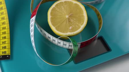 сантиметр : A multi-colored centimeter and a half of fresh lemon are on the aquamarine floor scales. Healthy foods and weight management tools Стоковые видеозаписи