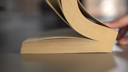 irodalom : Man leafs through an old book turning over pages on a gray surface. Slow motion. Knowledge concept Stock mozgókép