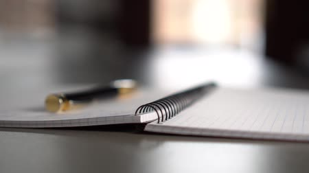 füller : A black-gold pen lies on an open notebook on a gray table in front of a window. The concept of life planning and working day in business