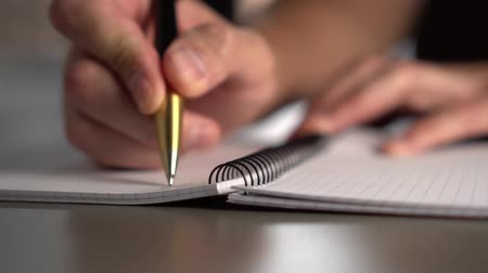 abriu : A man writes with a yellow black pen in an open notebook on a gray table, the light from the window illuminates the workplace. slow motion Vídeos