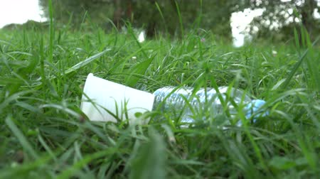 atmak : Plastic trash falls on the lawn onto the green young grass. The problem of garbage thrown out in nature