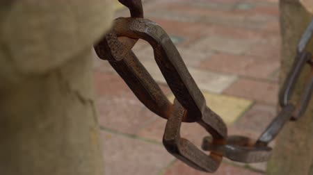 던지기 : Ancient large metal chain on a wooden post. The concept of reliability and durability forever