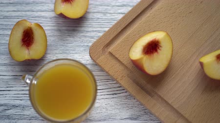 нектар : Glass mug with juice on a wooden table with sliced peaches and a kitchen board. Fruit diet
