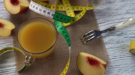 сантиметр : Peaches, juice and a fork on a sackcloth and a wooden table with a centimeter. Fruit diet Стоковые видеозаписи