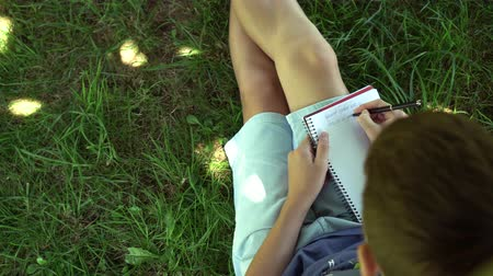 fiatalos : A teenager is reading a book sitting on the grass near a tree. Blue tank top and pigeon shorts. Dark hair. Exam preparation Stock mozgókép