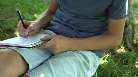 roman : A teenager is reading a book sitting on the grass near a tree. Blue tank top and pigeon shorts. Dark hair. Exam preparation Stok Video