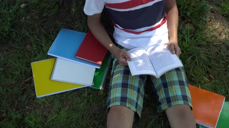 fiatalos : A teenager is reading a book sitting on the grass near a tree. Multi-colored T-shirt and shorts. Bright notebooks lie nearby