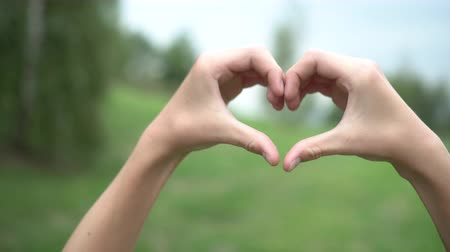 conifère : Teen joins hands in the shape of a heart on a background of green trees and sky in the park Vidéos Libres De Droits