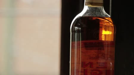 nightcap : reflections in still whiskey bottle Stock Footage