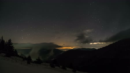 snowy background : Starry night sky with stars and low clouds moving over mountains. Time lapse zoom in