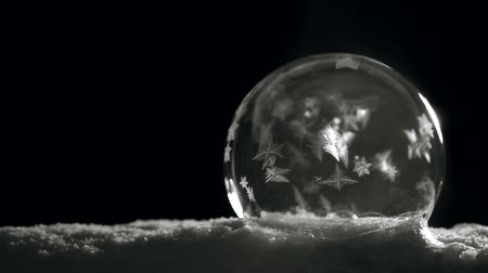 törékeny : Ice crystal ball freezing on snow on black background
