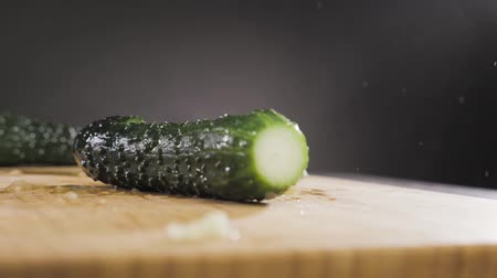 Hand hits a cucumber with a large knife