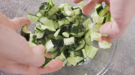 Hands mix cucumbers in a glass bowl