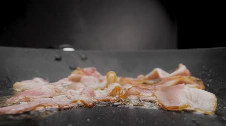 The bacon is fried in a pan. Stok Video