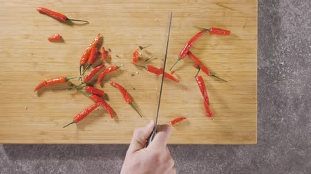 Hand cuts red hot pepper.