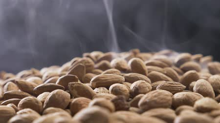 Smoke rises through almonds which spin on a black background