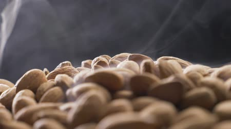 high rises : Smoke rises through almonds which spin on a black background