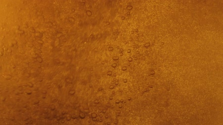 варево : Orange liquid is poured into a glass. Many rising bubbles
