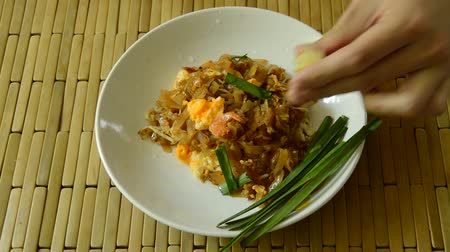 soğancık : hand squeeze lemon lime on Pad Thai stir fried rice noodles mixed and scooping by fork to eat